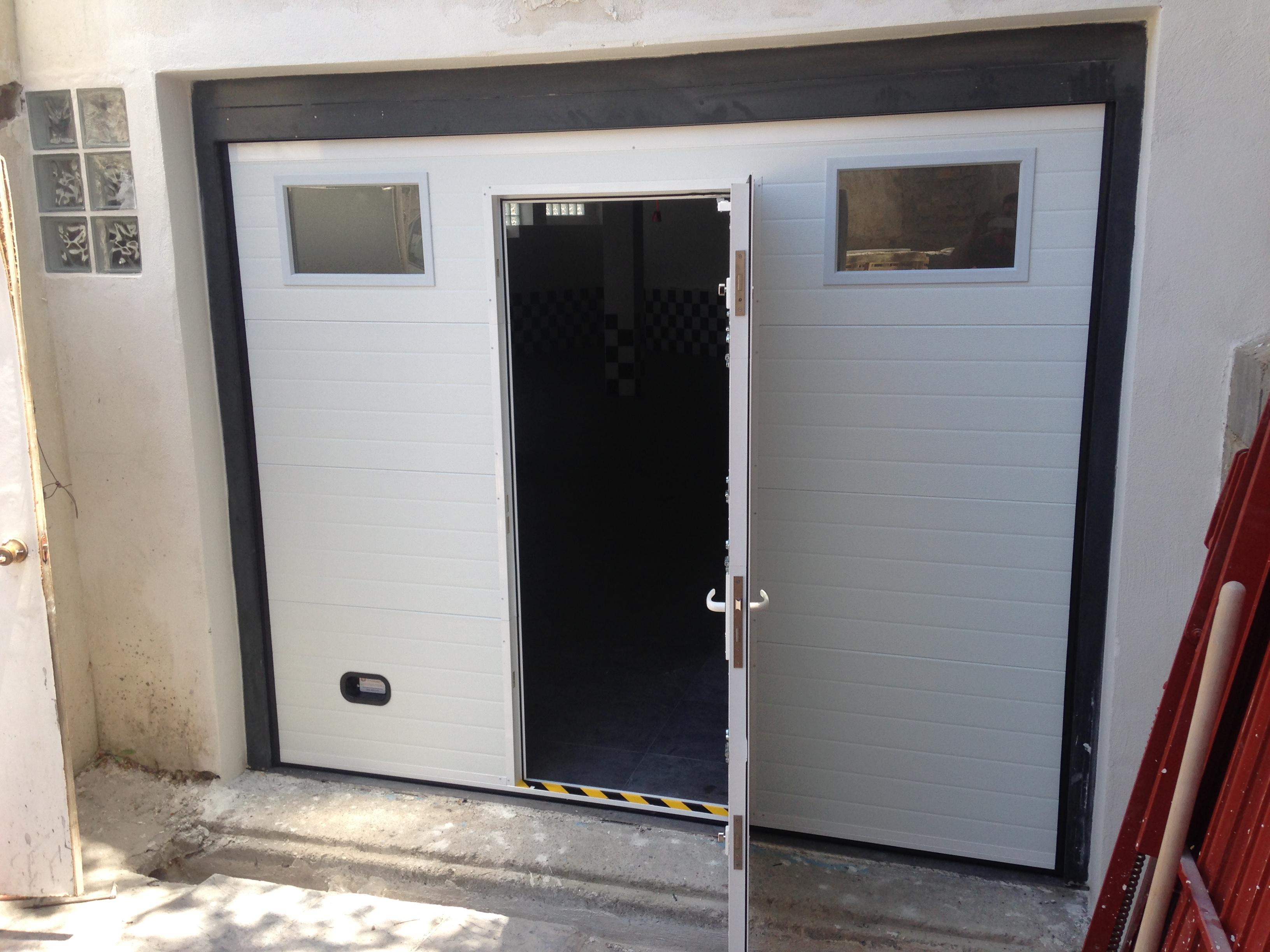 Puerta seccional con puerta peatonal y ventanas doble for Puertas de garaje precios